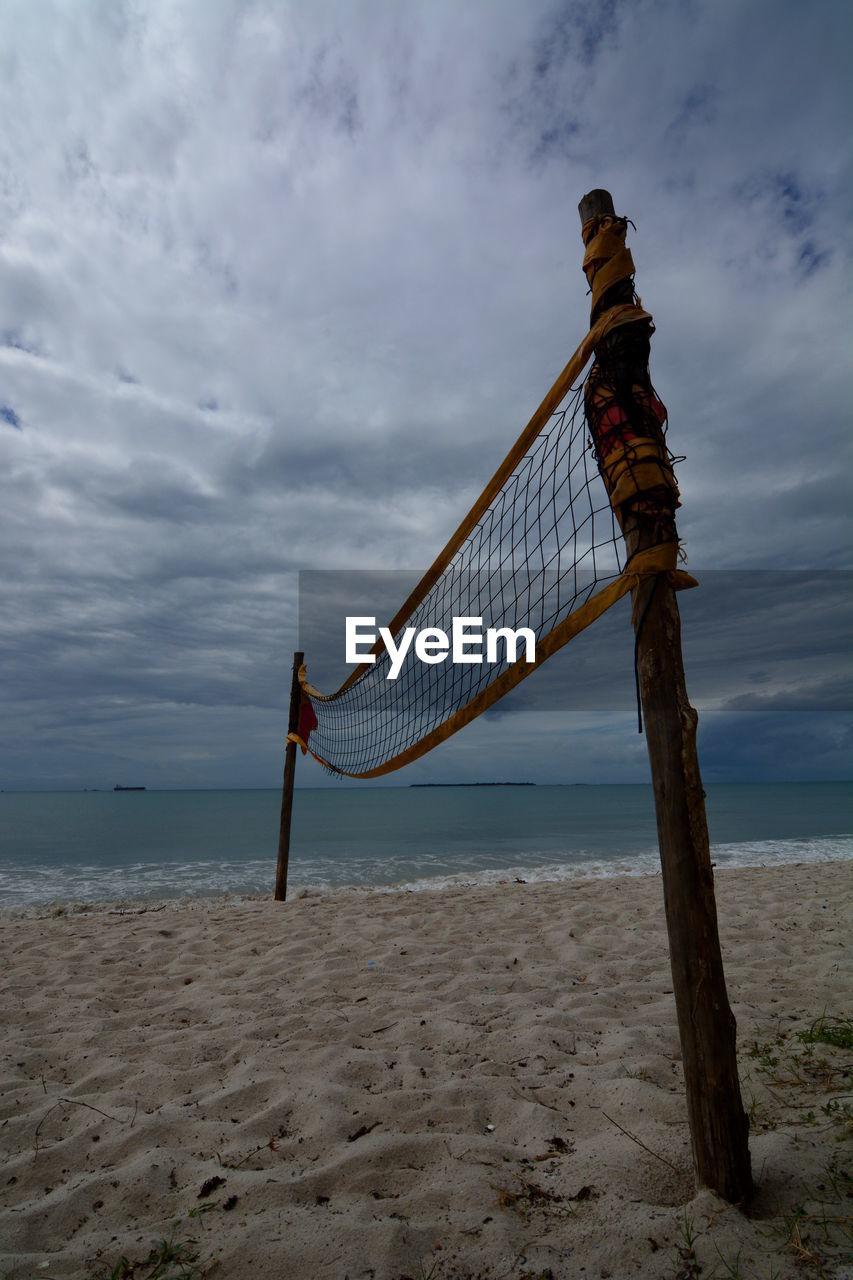 Volleyball net on sandy beach against cloudy sky
