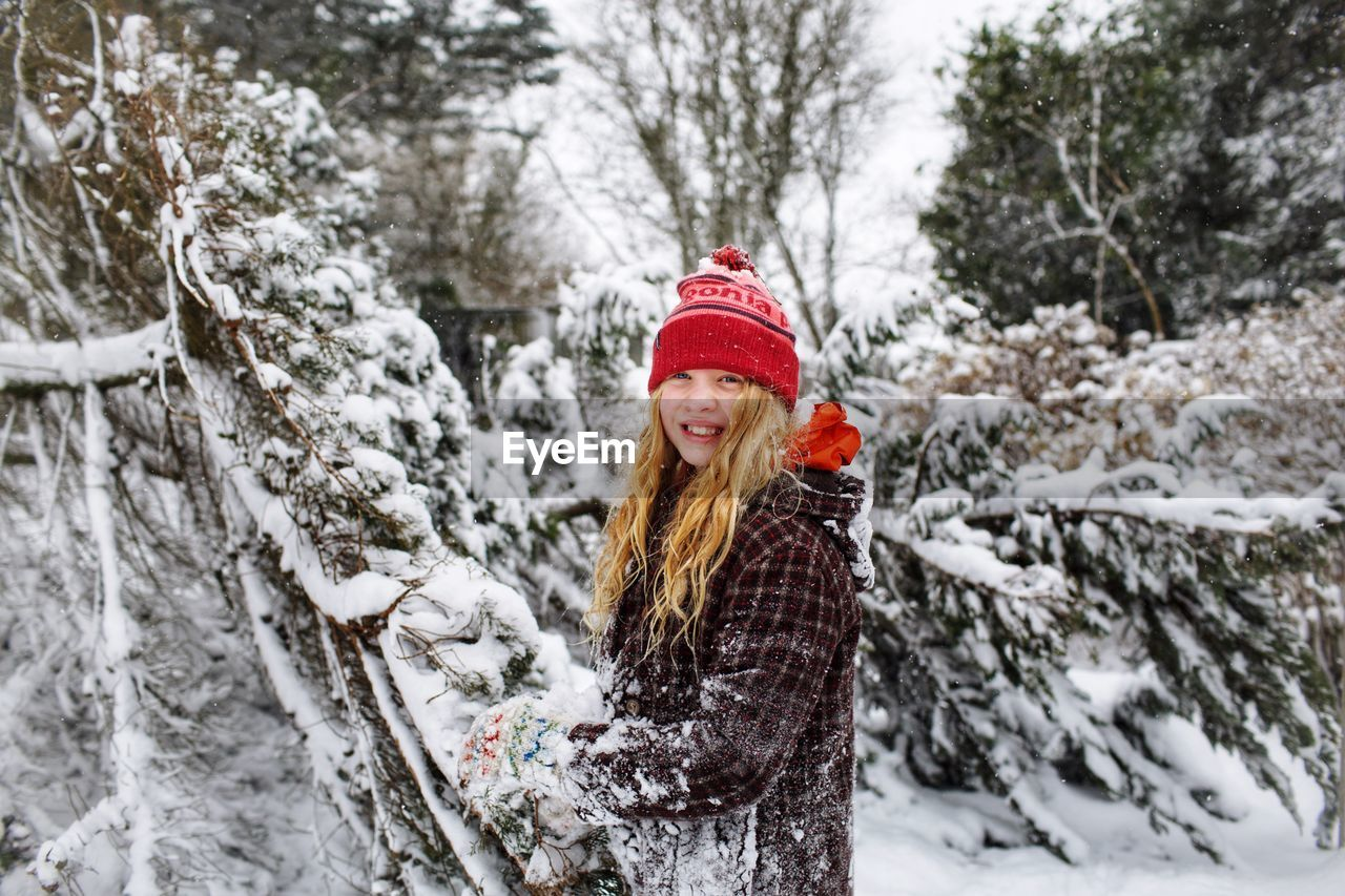 Portrait of smiling girl standing in forest during winter