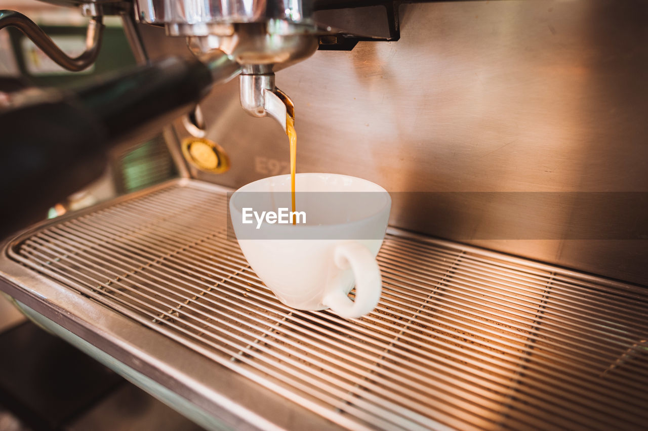 Close-Up Of Coffee Machine Pouring Latte In Cup At Cafe