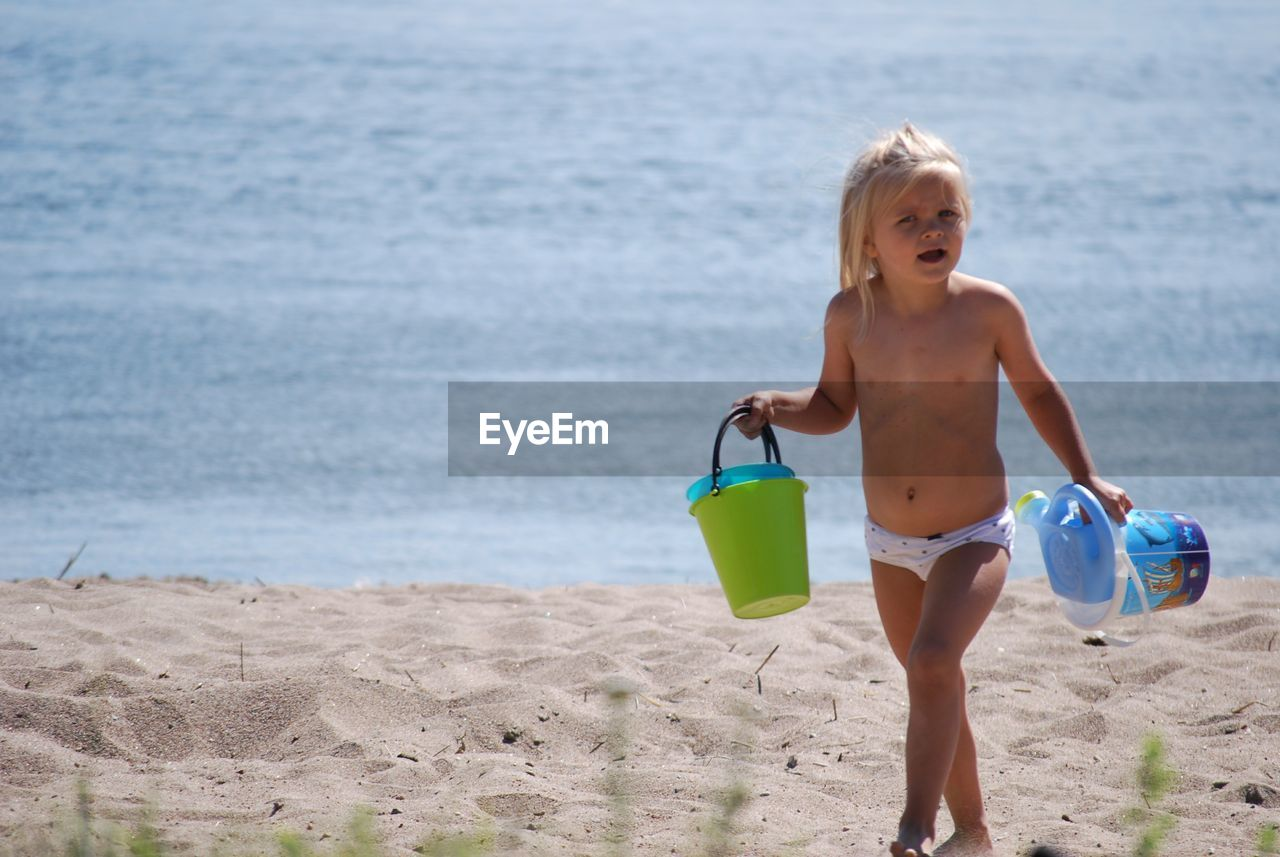 Shirtless Girl Carrying Buckets While Walking On Sand At Beach During Sunny Day