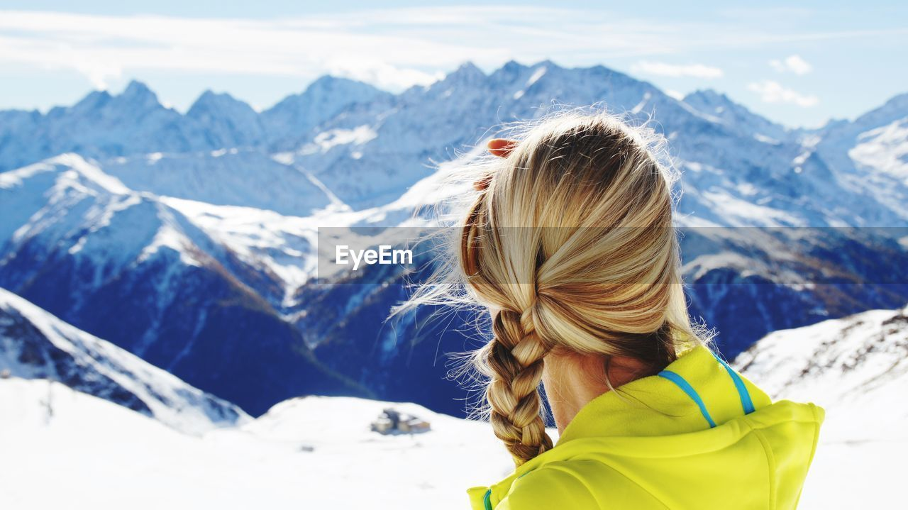 High Angle View Of Woman Standing On Snowcapped Mountain