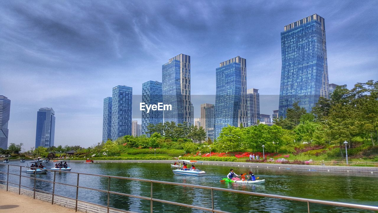 architecture, skyscraper, water, building exterior, built structure, sky, city, river, real people, modern, tower, waterfront, travel destinations, tree, large group of people, outdoors, day, urban skyline, travel, cloud - sky, men, nautical vessel, cityscape, women, people