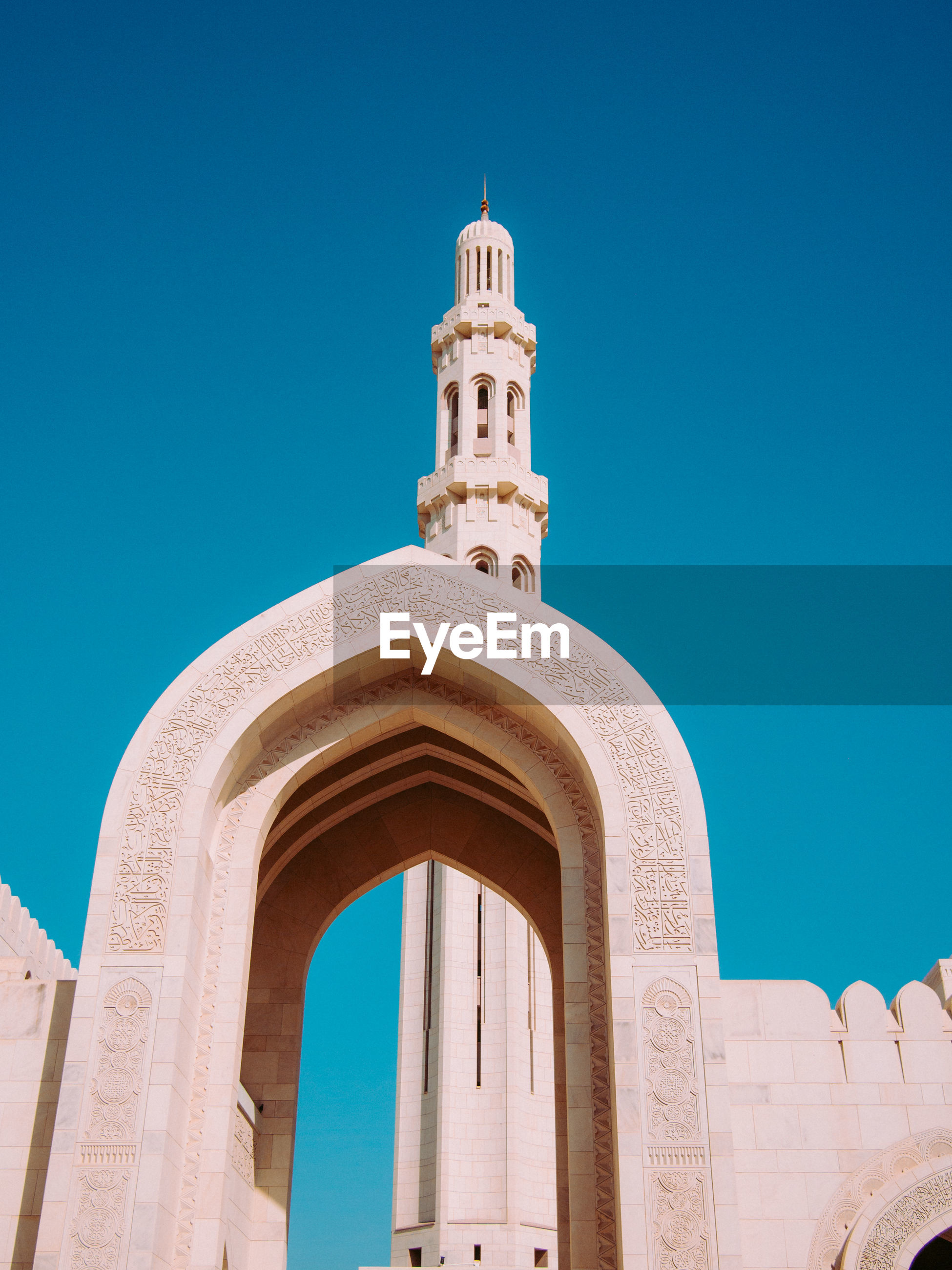 Low angle view of mosque entrance against clear blue sky