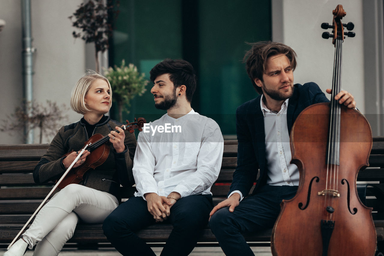 Performers With Musical Instruments Sitting On Bench