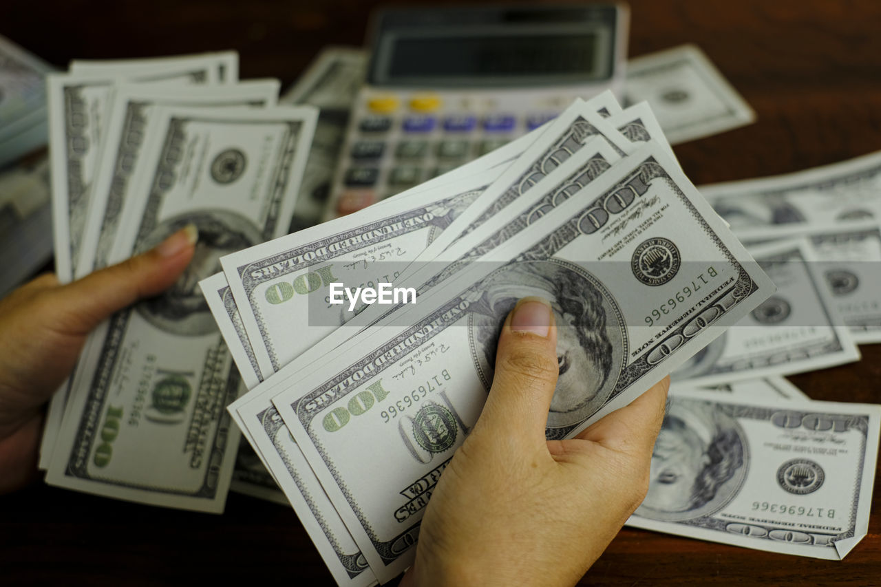 human hand, hand, human body part, business, currency, holding, finance, people, paper currency, unrecognizable person, wealth, real people, indoors, body part, paper, finger, close-up, economy