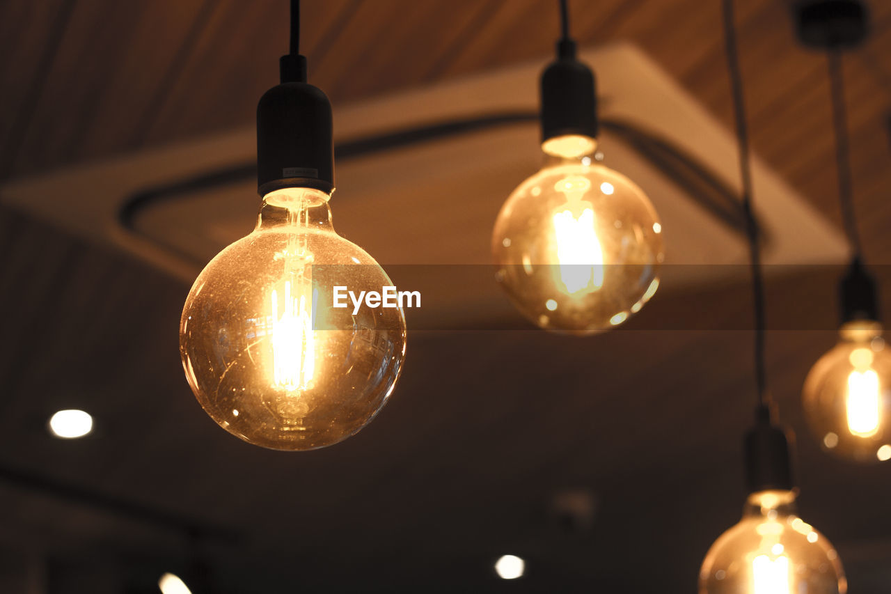 illuminated, electricity, lighting equipment, light bulb, hanging, indoors, glowing, light, no people, close-up, focus on foreground, electric light, low angle view, technology, pendant light, filament, bulb, cable, light - natural phenomenon, glass - material, ceiling, electrical equipment, electric lamp