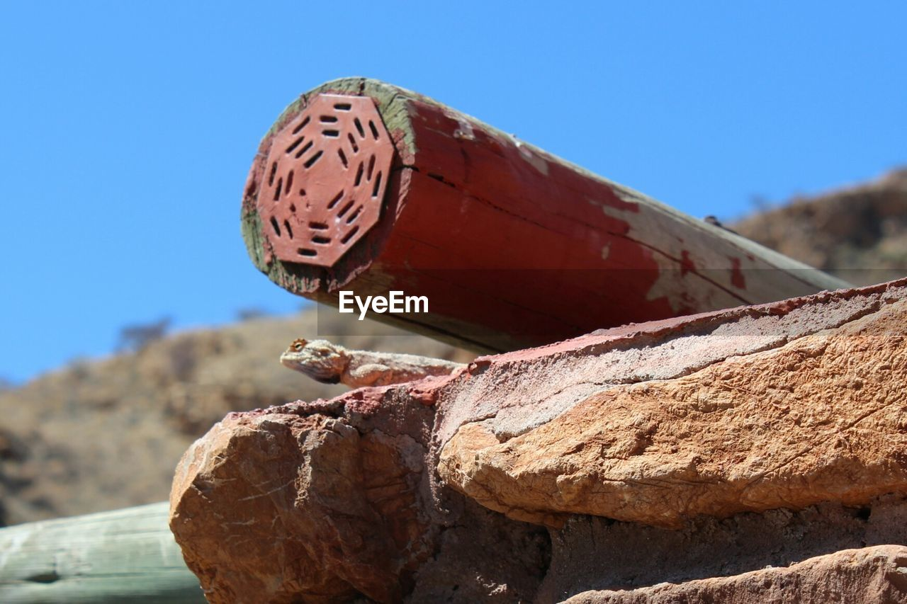 focus on foreground, sky, clear sky, day, nature, close-up, blue, sunlight, no people, abandoned, metal, outdoors, low angle view, old, land, rusty, brown, red, solid, rock