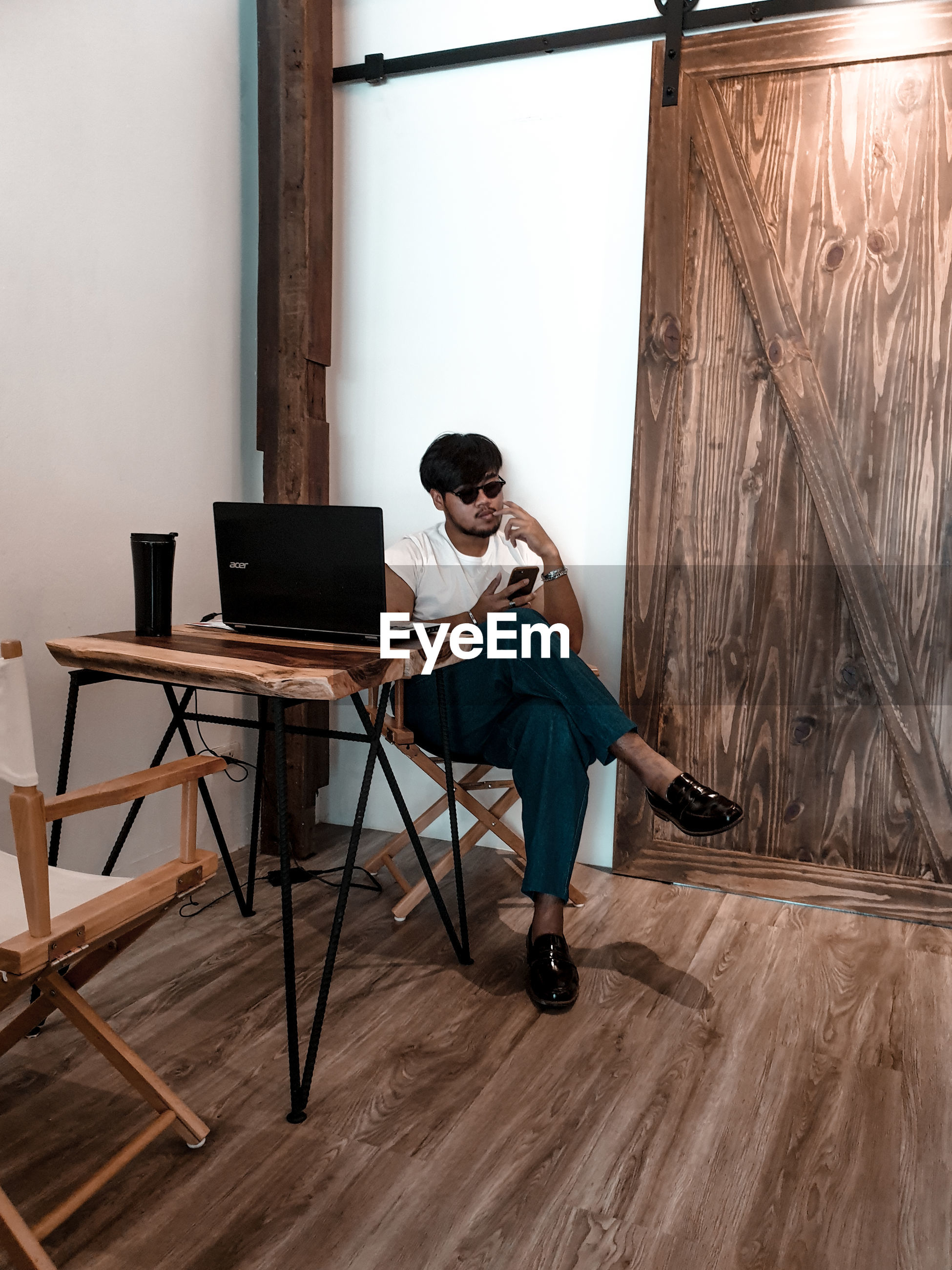 Full length of man using mobile phone while sitting on wooden table