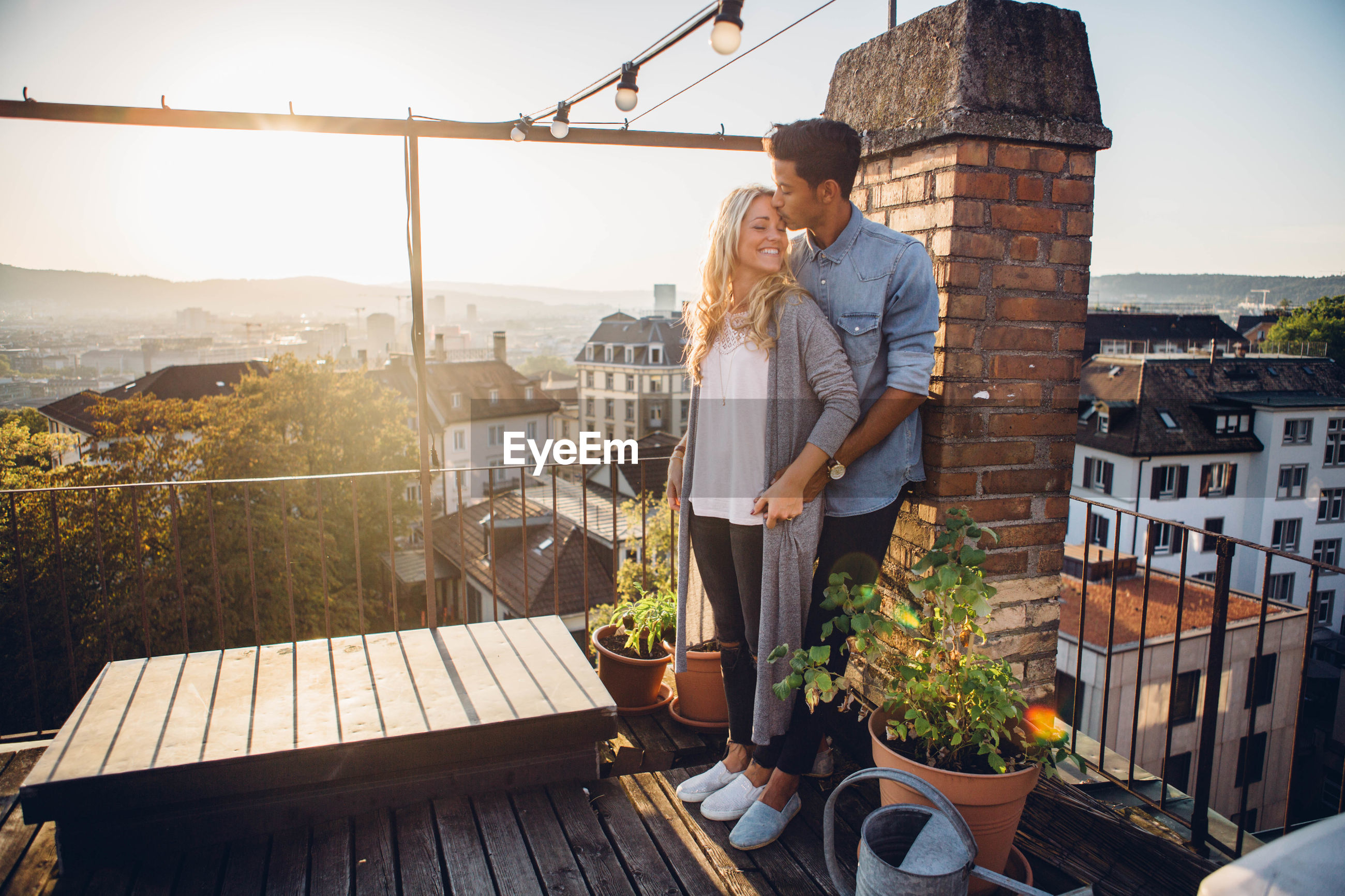 Couple standing at building terrace against sky