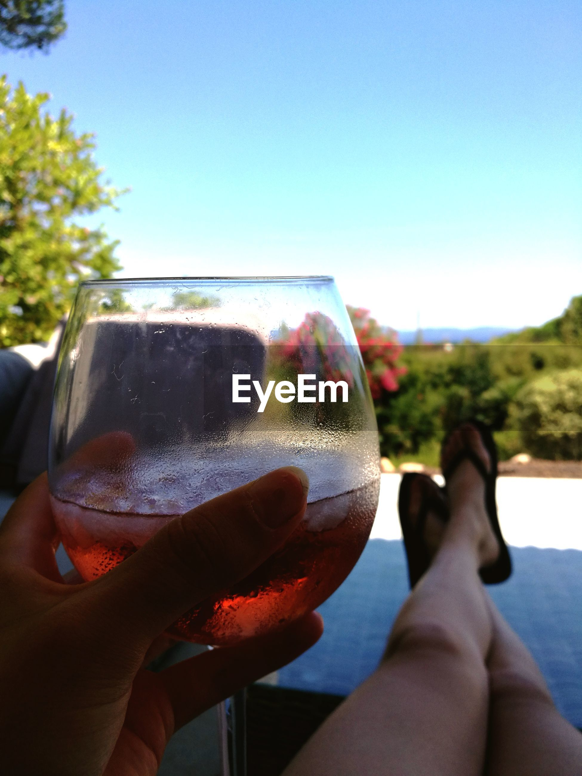 Low section of woman holding wineglass while resting outdoors