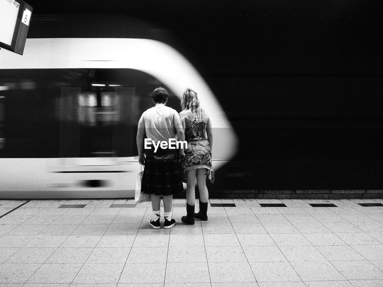 Rear View Of Man And Woman At Railroad Station