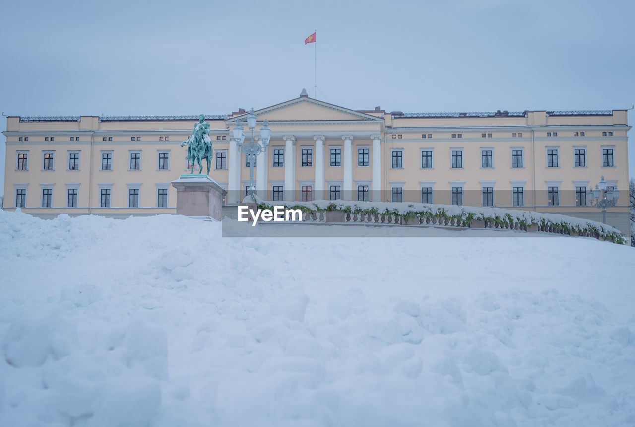 Snow covered field in front of royal palace against sky during winter