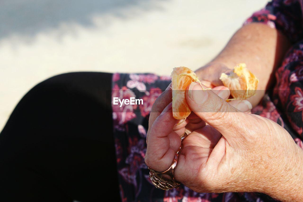 Close-Up Of Hands Holding Orange Slices