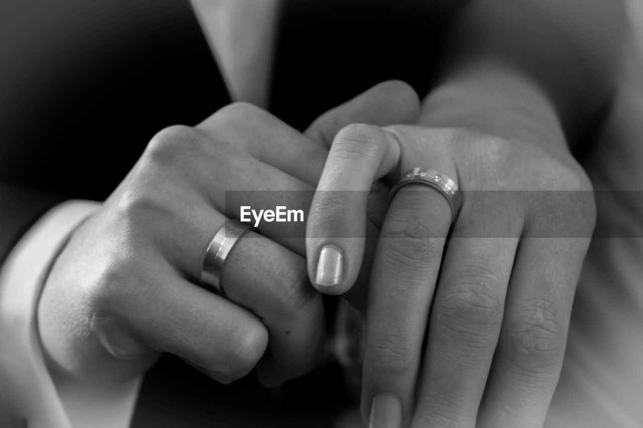 Cropped Image Of Couple Wearing Finger Rings And Holding Hands