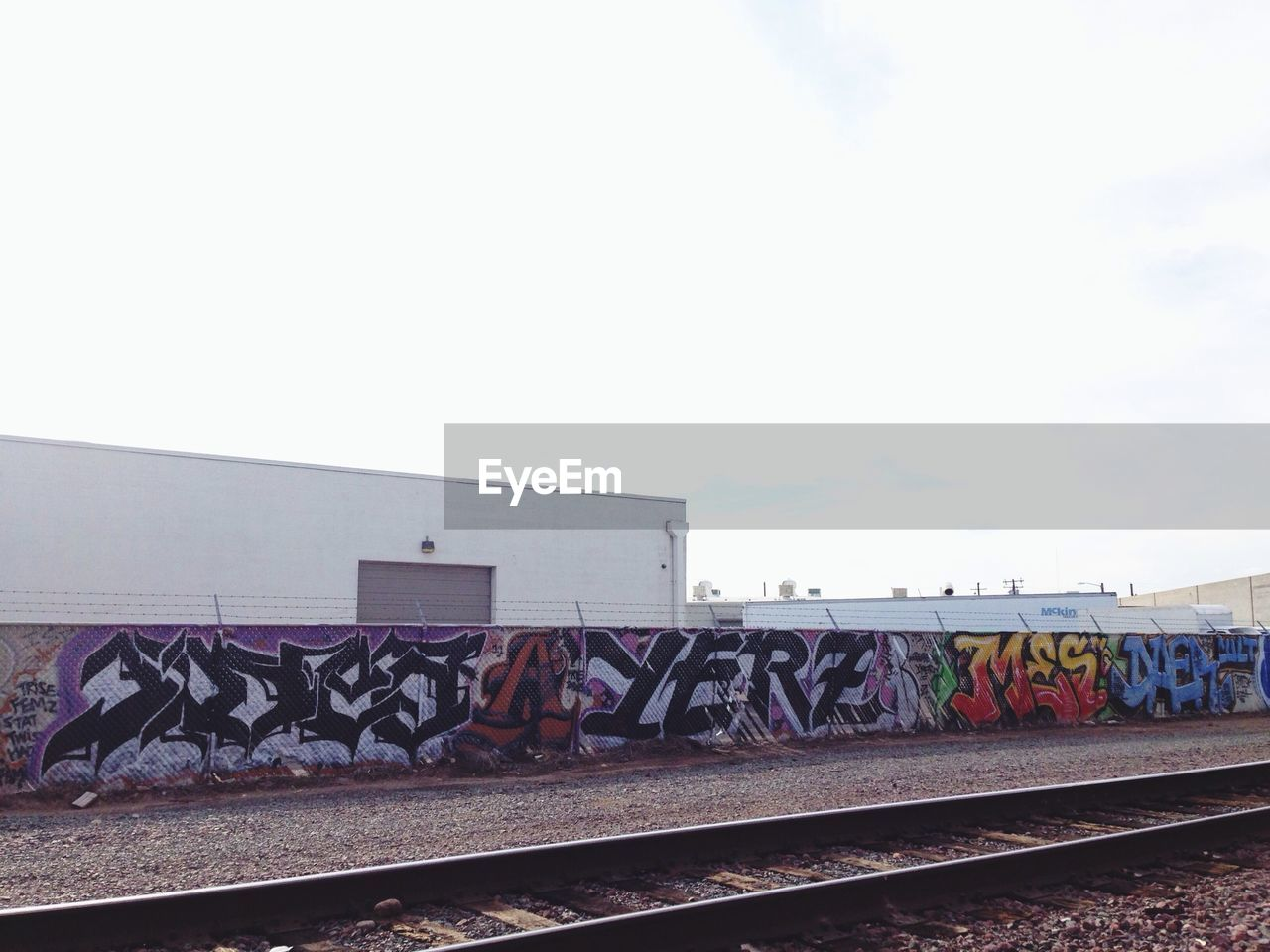 railroad track, rail transportation, graffiti, copy space, transportation, day, sky, outdoors, no people, clear sky, multi colored