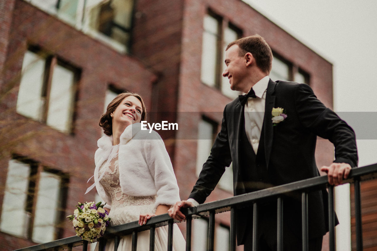 Low Angle View Of Smiling Couple Standing Against Building
