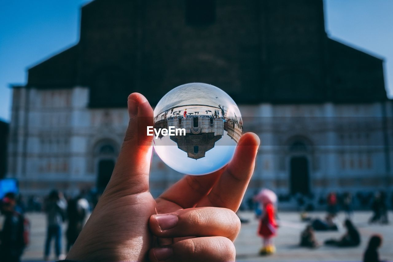 Close-up of hand holding crystal ball with city in background - san petronio, bologna