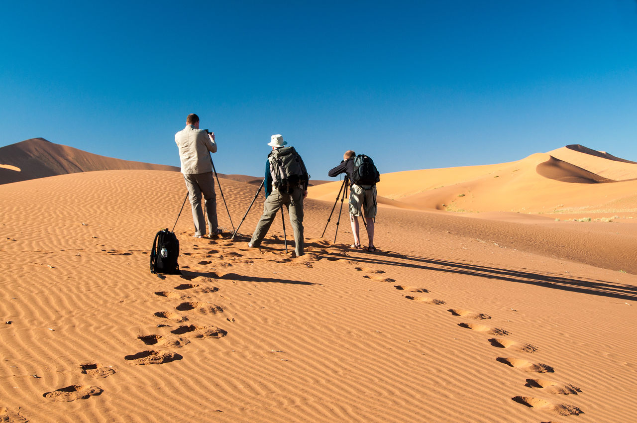 People On Sand Dune In Desert Against Clear Sky