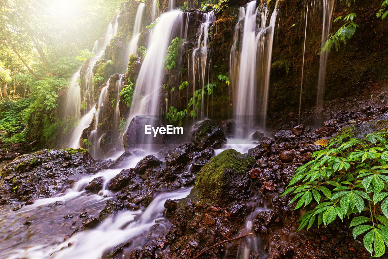 beauty in nature, scenics - nature, water, long exposure, rock, waterfall, land, flowing water, forest, nature, motion, blurred motion, plant, tree, solid, rock - object, non-urban scene, no people, environment, flowing, outdoors, rainforest, falling water, power in nature