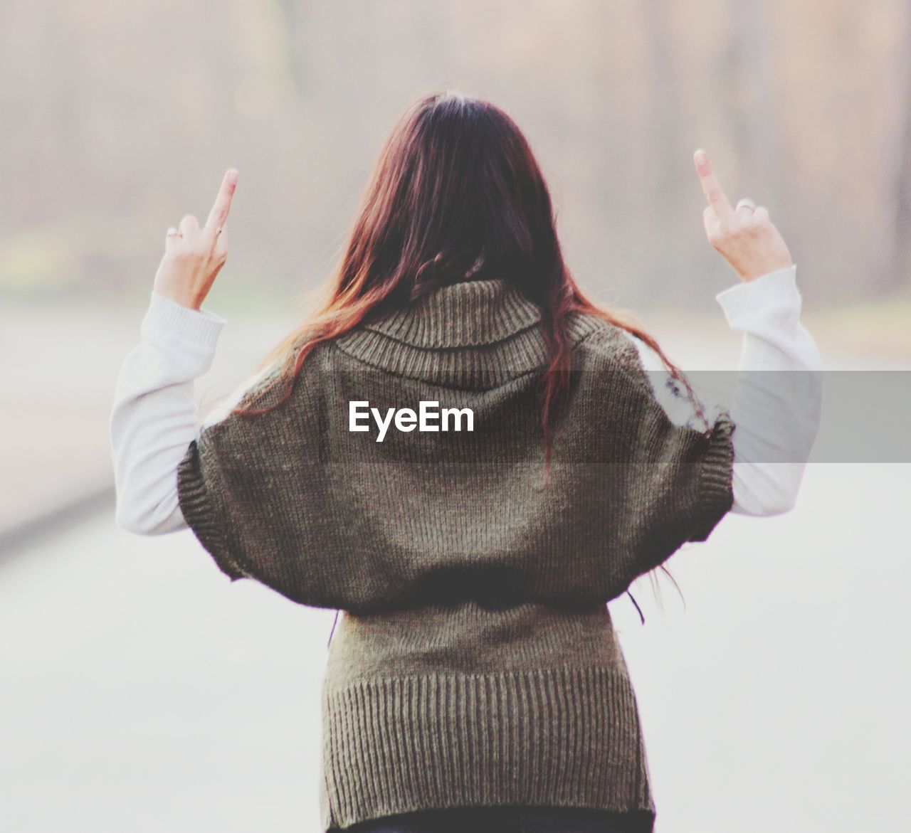 Rear view of woman showing middle fingers