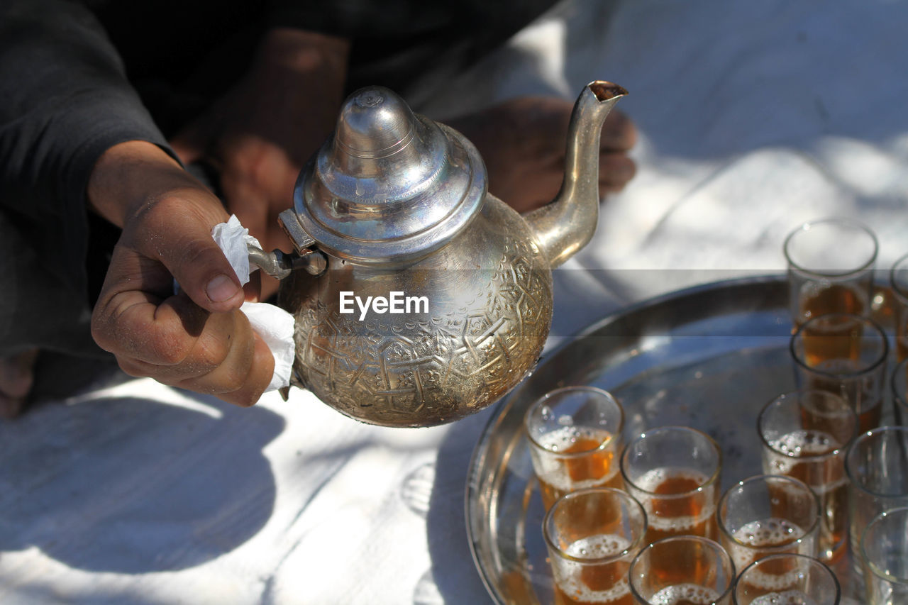Cropped image of man hand pouring mint tea in glass