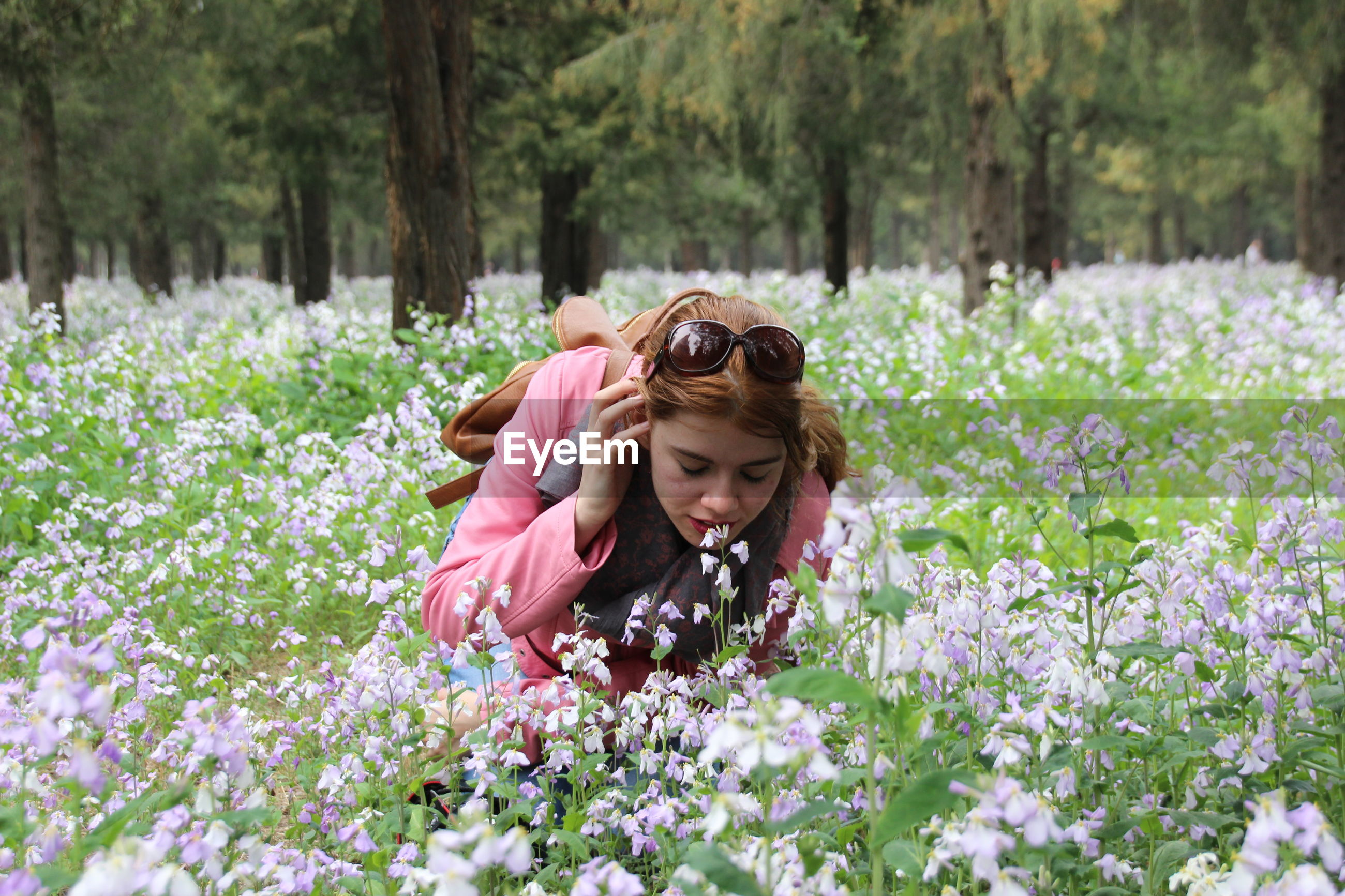 Beautiful woman smelling flowers on land