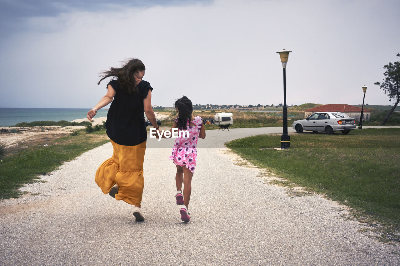 two people, child, sky, real people, full length, girls, childhood, females, togetherness, women, road, transportation, family, casual clothing, nature, rear view, leisure activity, bonding, positive emotion, lifestyles, sister, outdoors