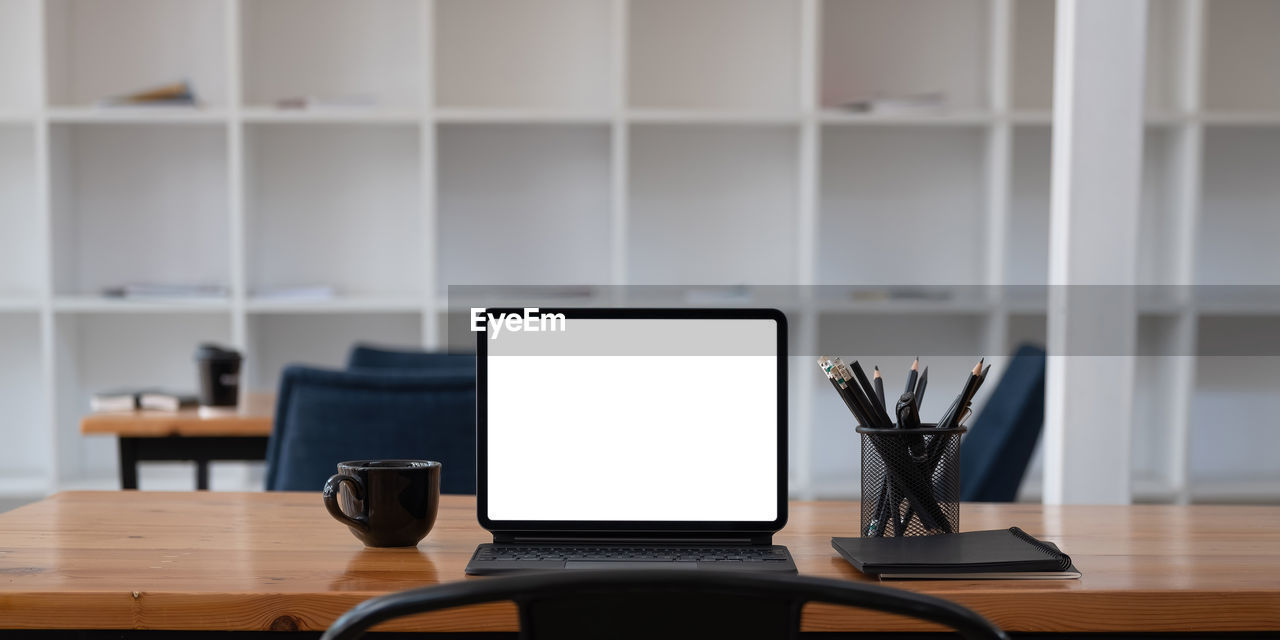 Cropped shot of workplace with tablet blank screen and office supplies in simple workspace