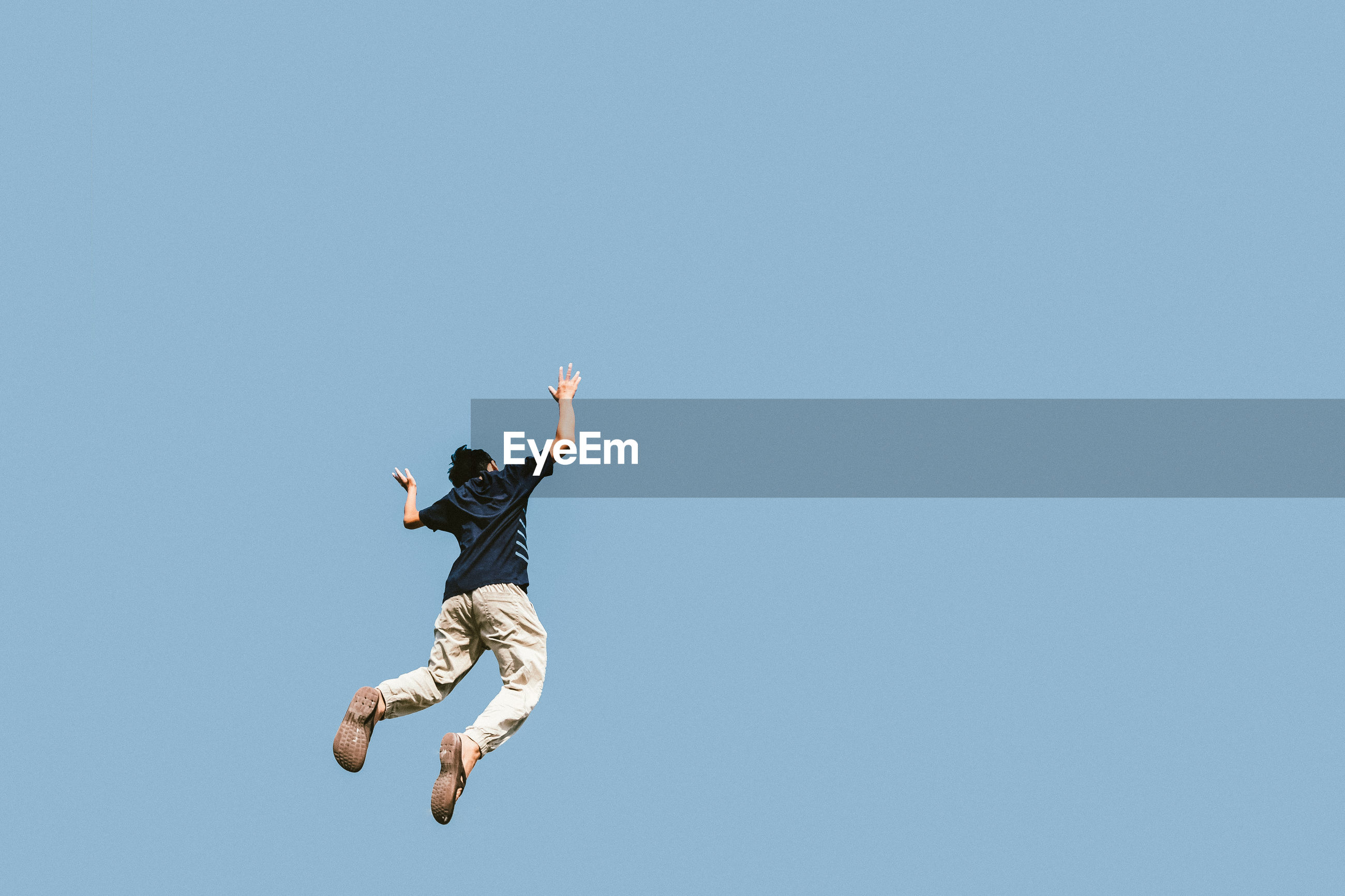 LOW ANGLE VIEW OF MAN JUMPING AGAINST BLUE SKY