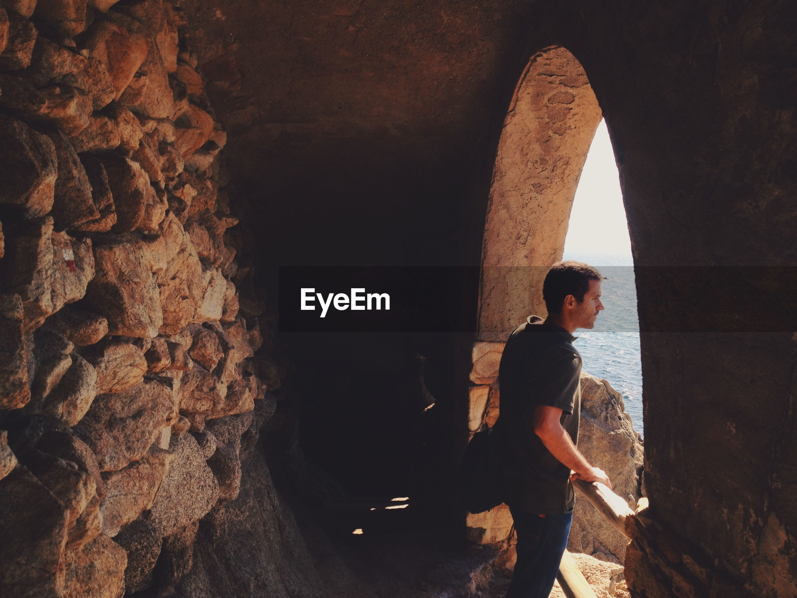 Side view of young man looking through arch window from cave