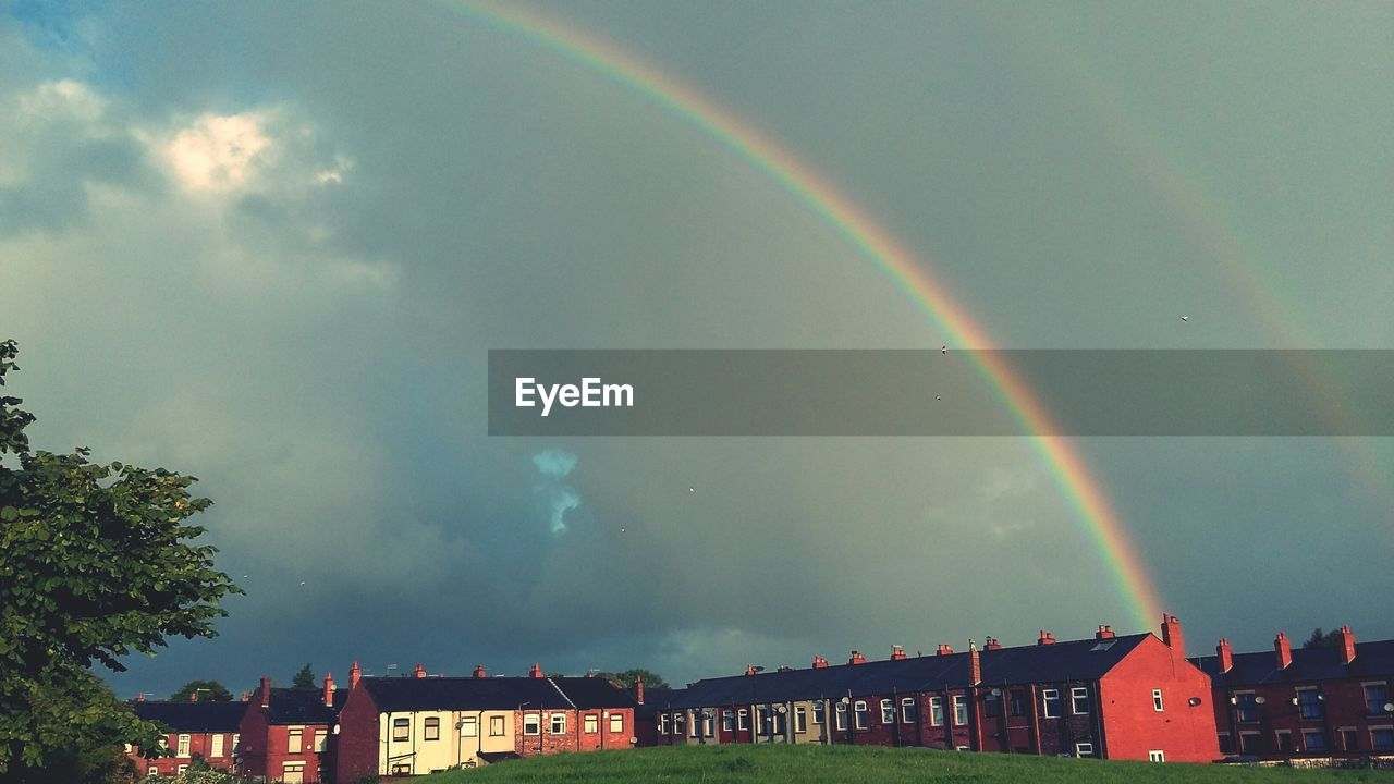 Low angle view of double rainbows above buildings