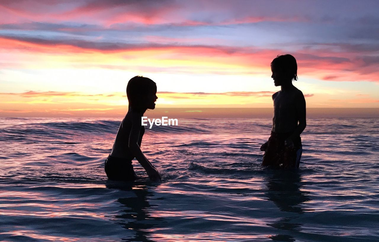 Siblings swimming in sea against sky during sunset