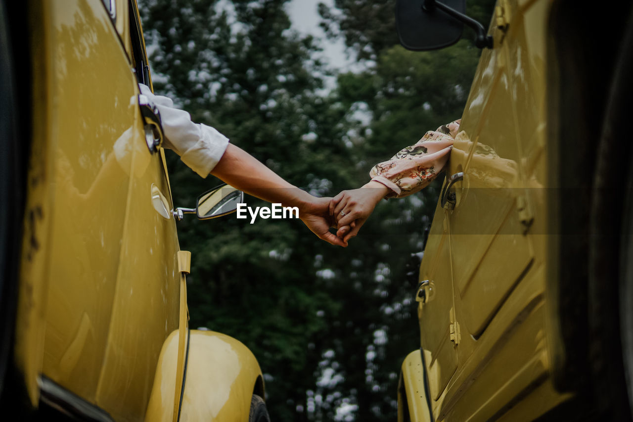 Cropped image of people holding hands while sitting in car
