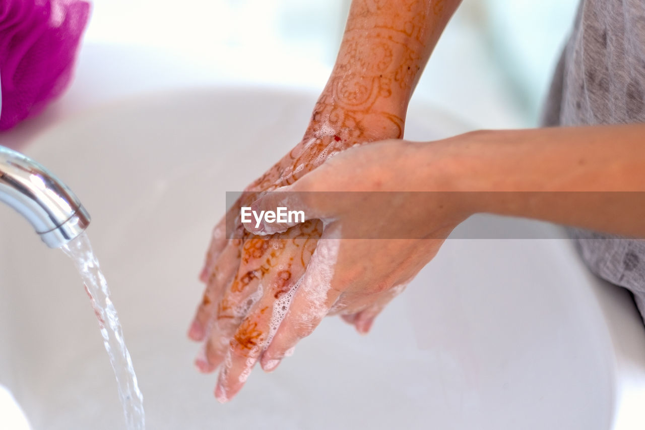Close-up of woman washing hands at sink