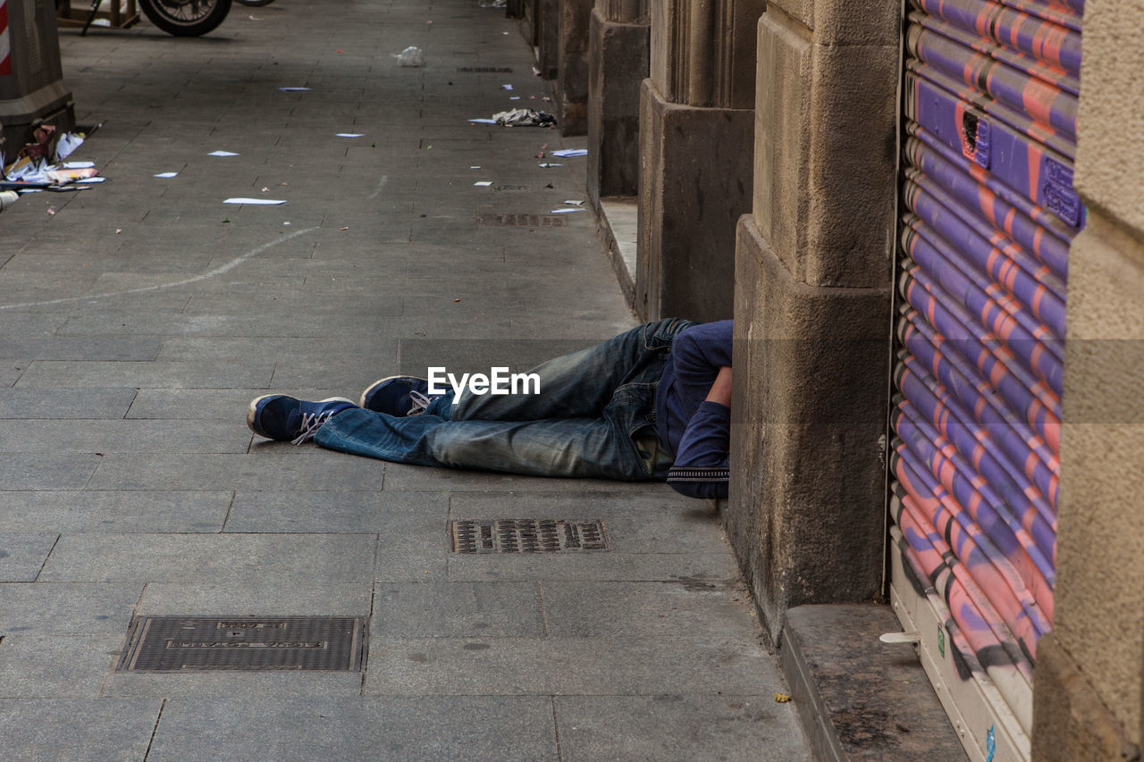 sleeping, social issues, relaxation, city, one person, lying down, street, architecture, men, casual clothing, real people, full length, lying on back, footpath, resting, sidewalk, despair, hopelessness