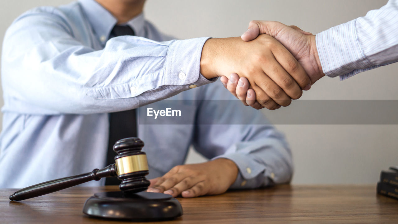 Midsection of lawyer shaking hand with man in office