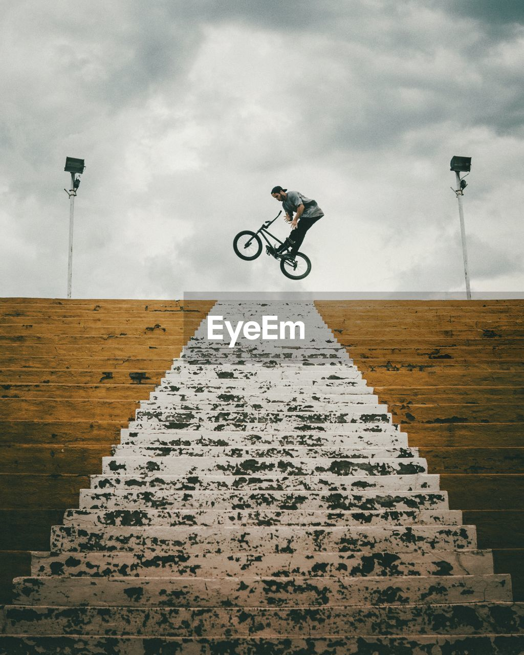Low angle view of young man jumping with bicycle on steps against cloudy sky