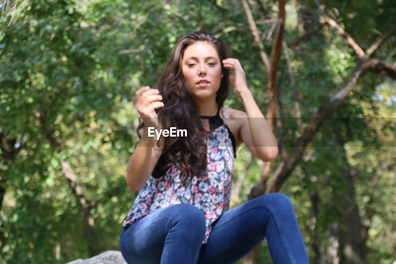 one person, sitting, tree, young adult, three quarter length, leisure activity, front view, casual clothing, plant, hair, lifestyles, day, long hair, hairstyle, young women, looking at camera, real people, portrait, outdoors, beautiful woman, contemplation