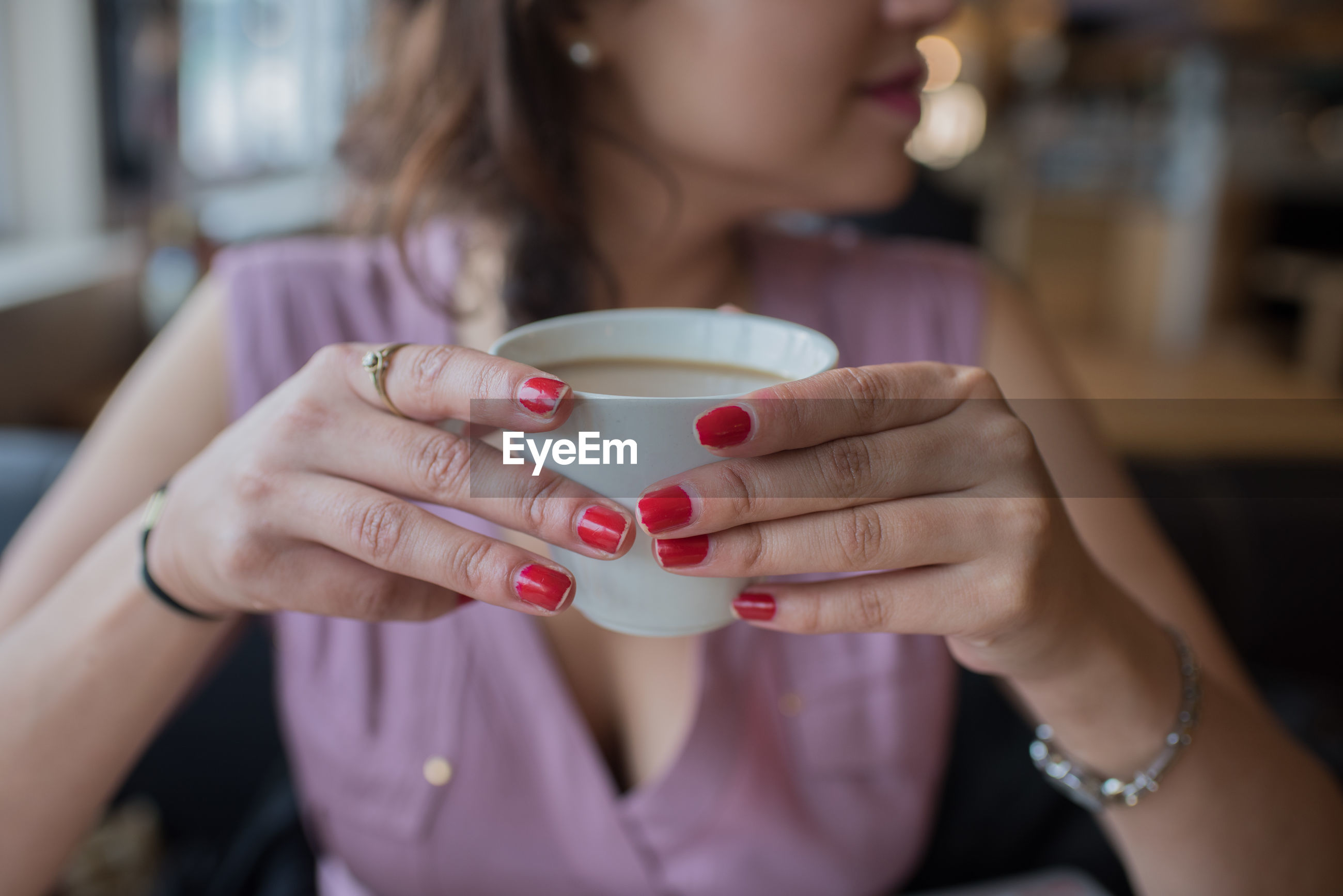 Midsection of woman having coffee in cafe