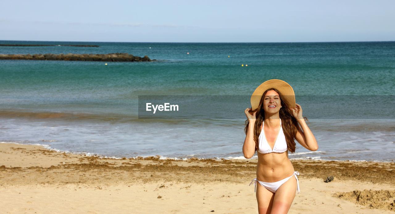 Portrait of cheerful woman wearing bikini while standing at beach