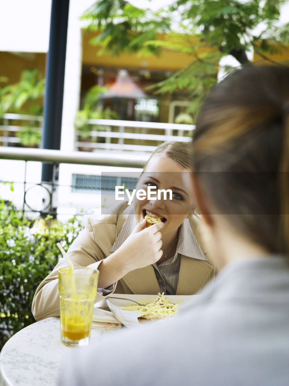 Portrait Of Businesswoman With Colleague Eating Food At Cafe