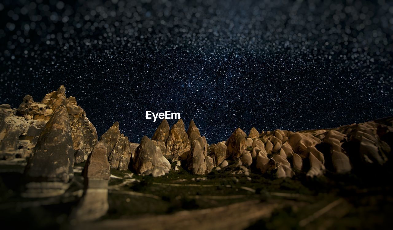 Standing Rocks On Landscape Against Starry Sky