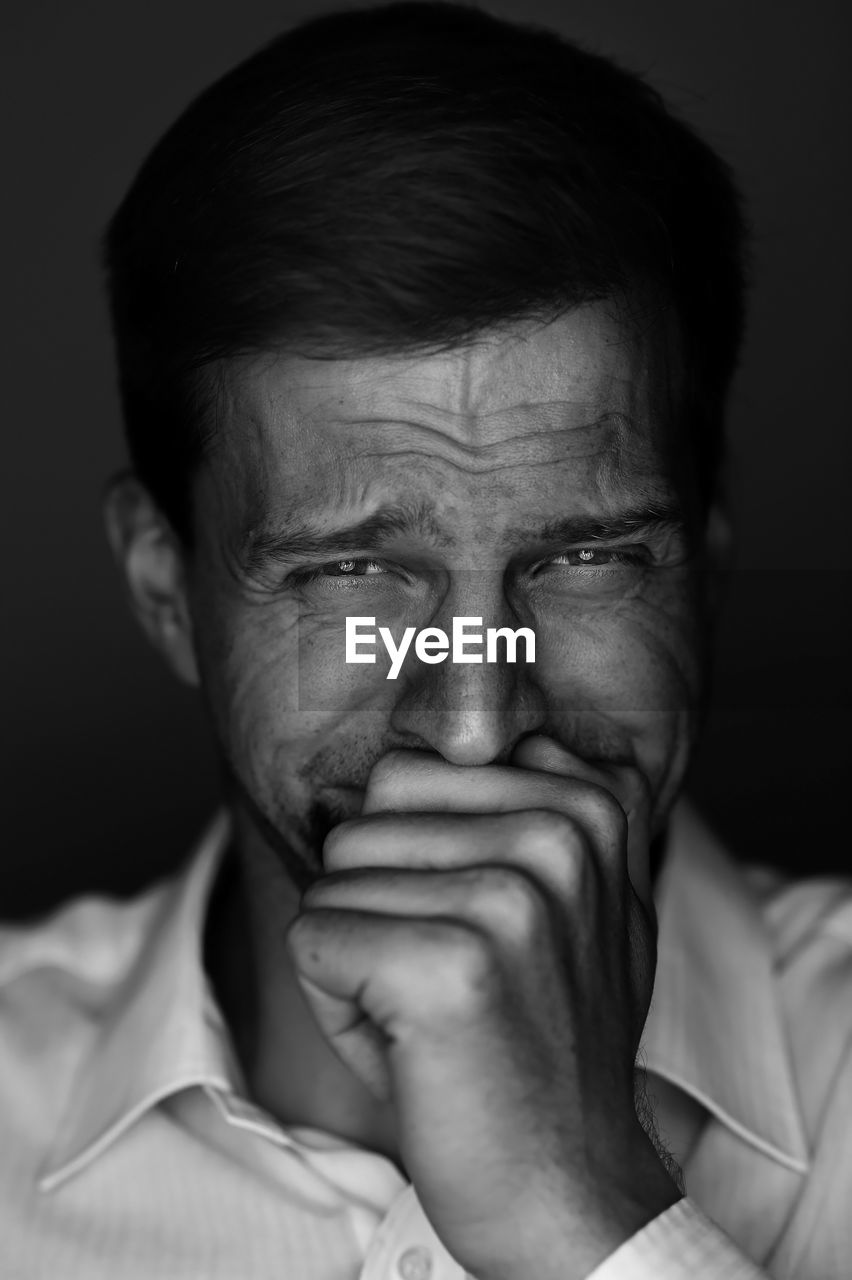 Close-Up Portrait Of Mid Adult Man Crying Against Black Background