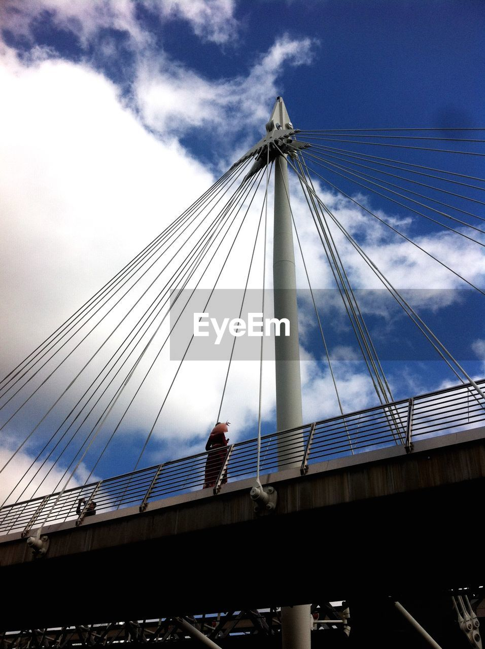 bridge - man made structure, connection, engineering, suspension bridge, architecture, sky, built structure, bridge, low angle view, cloud - sky, transportation, outdoors, day, city, cable, men, real people, people