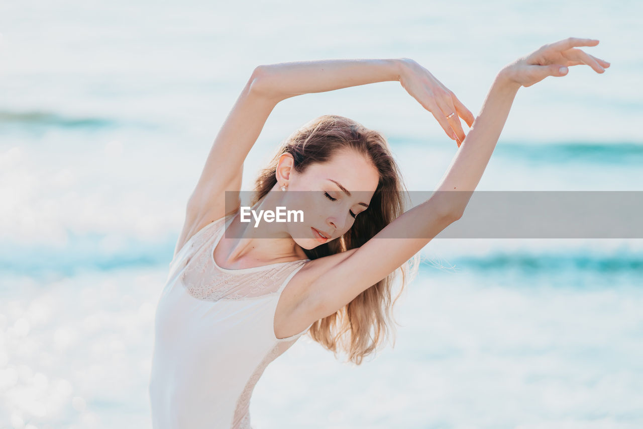 Beautiful young woman dancing with eyes closed at beach against sea
