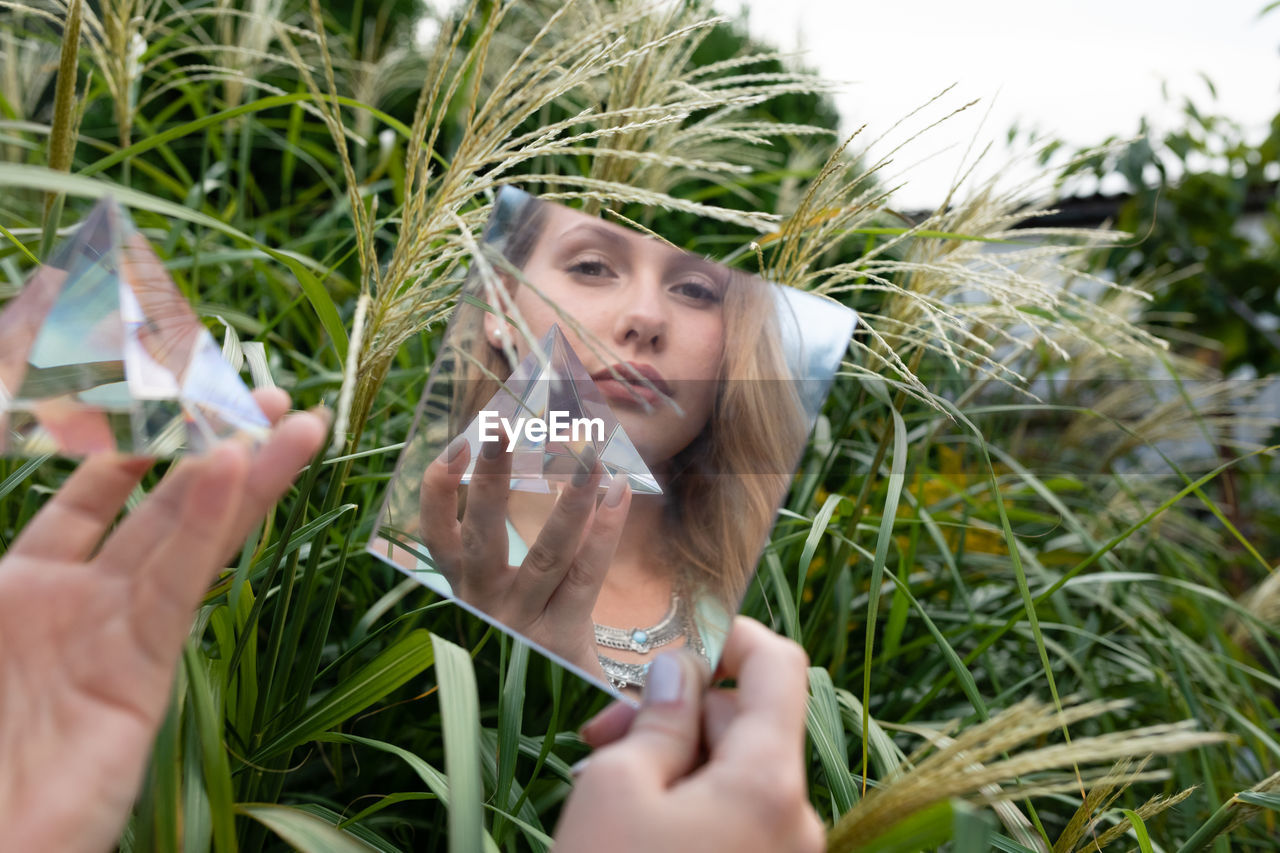 Reflection of woman looking away and holding prism in mirror against plants