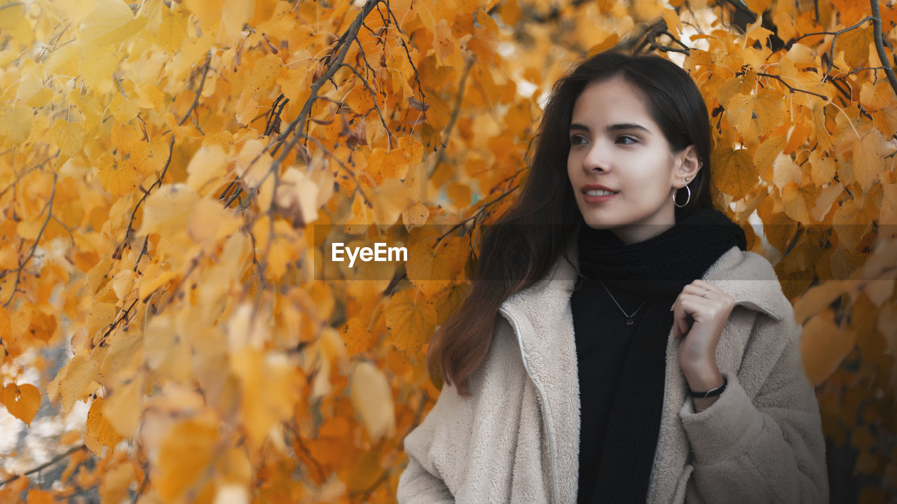 Young woman standing against maple leaves during autumn