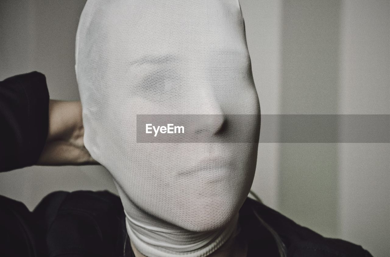 Close-Up Portrait Of Woman Covering Face With Fabric