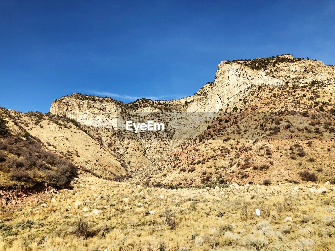sky, blue, mountain, tranquil scene, beauty in nature, nature, clear sky, rock, scenics - nature, tranquility, rock formation, day, no people, environment, sunlight, rock - object, mountain range, non-urban scene, solid, low angle view, formation, arid climate, outdoors, climate, eroded, mountain peak