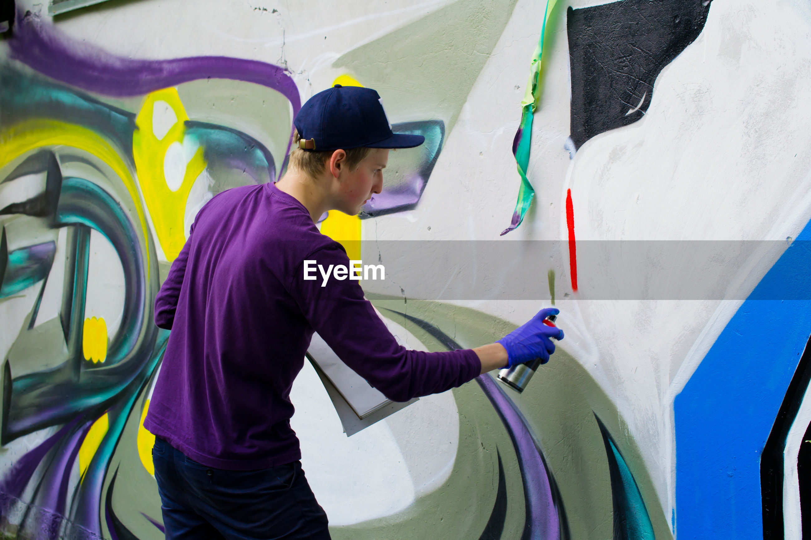 Man spray painting wall